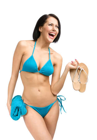 Portrait of woman wearing bikini and handing towel and thongs, isolated on white. Concept of summer holidays and traveling photo