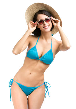 Portrait of female wearing bikini, hat and sunglasses, isolated on white. Concept of summer holidays and traveling photo