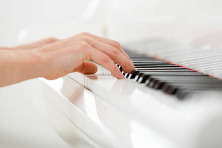 Close up of hands playing piano. Concept of music and entertainment photo