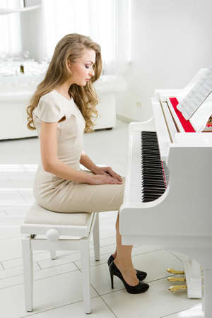 Profile of woman sitting on bench and looking at piano. Concept of music and art photo