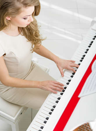 Top view of woman playing piano. Concept of music and art photo