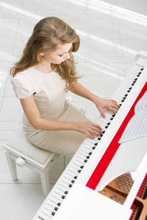 instrumentalist: Top view of woman wearing beige dress and playing piano. Concept of music and art