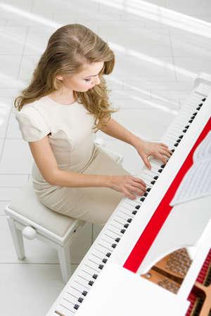 tocando piano: Vista superior de la mujer con vestido de color beige y tocar el piano. Concepto de la música y el arte