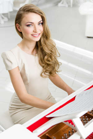 Portrait of woman wearing beige dress and playing piano. Concept of music and art Stock Photo - 24481046