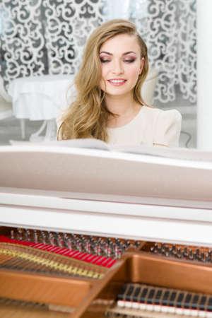 tocando piano: Retrato de mujer sentada y tocando el piano. Concepto de la música y el ocio Foto de archivo