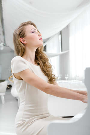 Side view of woman playing piano. Concept of music and art Stock Photo - 24481050