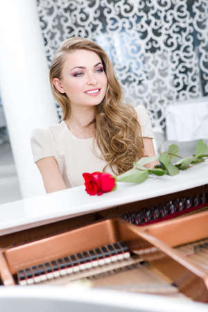 Portrait of woman with red rose playing piano. Concept of music and enjoyment Stock Photo - 24481052