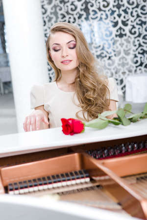 Portrait of woman with red rose playing piano. Concept of music and arts Stock Photo - 24481053
