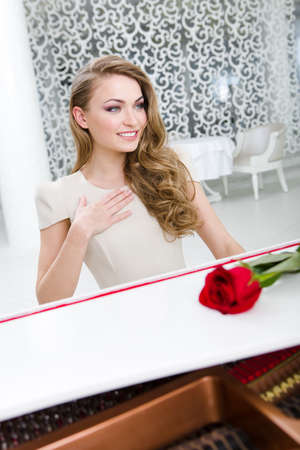 Portrait of woman with red rose playing piano. Concept of music and creative hobby Stock Photo - 24481056