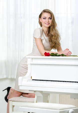 Portrait of woman in beige dress standing near the piano with red rose on it. Concept of music and arts Stock Photo - 24481060
