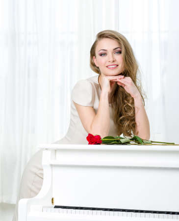 Portrait of woman in beige dress propping head and standing near the piano with red rose on it. Concept of music and art Stock Photo - 24481063