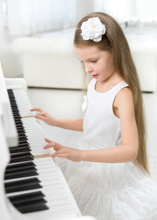 Portrait of little girl in white dress playing piano. Concept of music study and art Stock Photo - 24481066