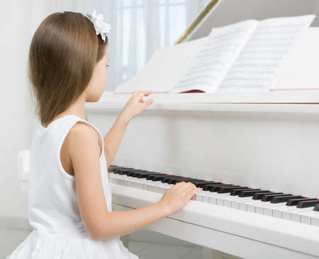 Side view of little girl in white dress playing piano. Concept of music study and art photo
