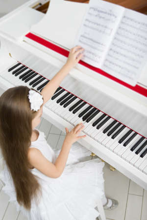 Top view of little girl in white dress playing piano. Concept of music study and art Stock Photo - 24481072