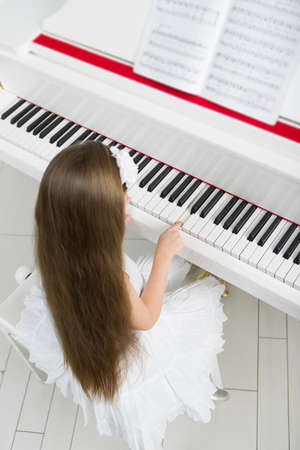 Top view of little girl in white dress playing piano. Concept of music study and arts photo
