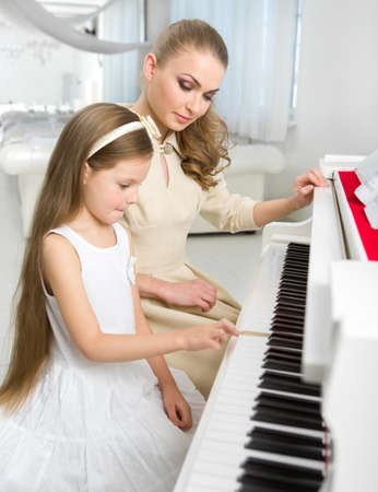 Tutor teaches little girl to play piano. Concept of music study and creative hobby Stock Photo - 24481076