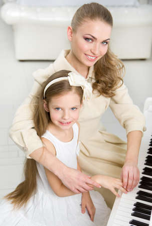 avocation: Tutor teaches little girl to play piano. Concept of music study and entertainment Stock Photo