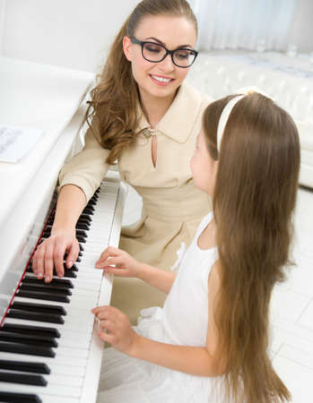 Tutor teaches little girl to play piano. Concept of music study and arts Stock Photo - 24481081