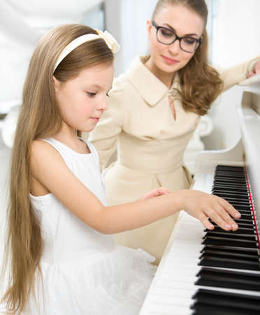 instrumentalist: Master teaches little girl to play piano. Concept of music study and creative hobby