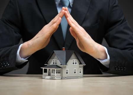 Gros plan des mains comme toit petite maison. Concept de l'immobilier et de la protection