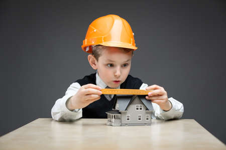 Portrait of little boy in headpiece with home model and ruler on grey background. Concept of real estate and engineering photo