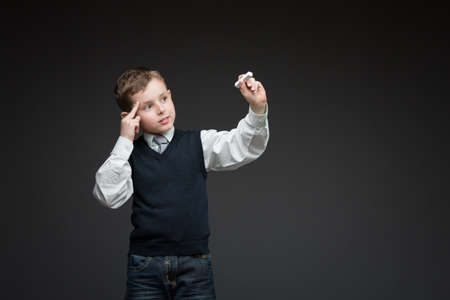 Portrait of pensive boy writing something with chalk on grey background, copyspace Stock Photo - 24481322