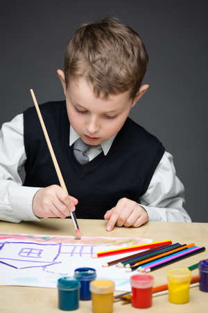Portrait of little boy painting something with paints and pencils. Concept of arts and hobby Stock Photo - 24481326