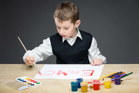 Portrait of little boy drawing energy formula with paints and pencils. Concept of arts and hobby Stock Photo - 24481325