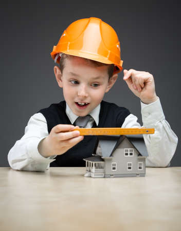 Portrait of little boy in hard hat with house model and ruler on grey background. Concept of real estate and engineering photo