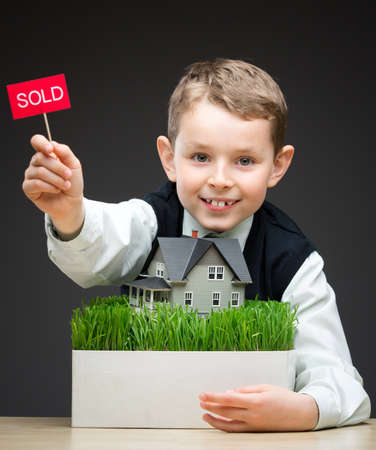 Portrait of little boy keeping home model and sold tablet on grey background. Concept of real estate and deal photo