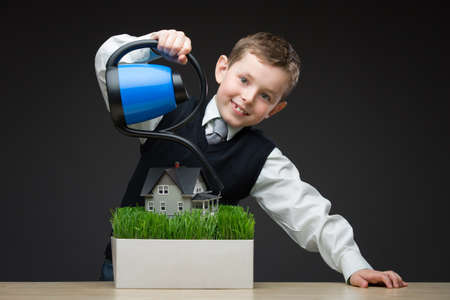 Portrait of little boy pouring house model and green grass with the help of watering pot. Concept of investment and real estate photo