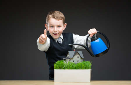 Portrait of little boy pouring home model and green grass with the help of watering pot. Concept of investment and real estate photo