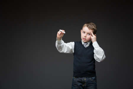 Portrait of pensive child writing something with chalk on grey background, copyspace Stock Photo - 24481411