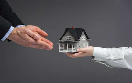 Close up of hands giving home model to other hands. Concept of realty and deal Stock Photo