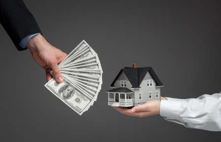 Close up of hands giving house model to other hands with money. Concept of real estate and deal photo