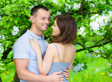 flowered: Couple embracing near flowered tree in the park. Concept of love and stable relations