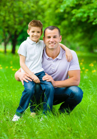 Dad keeps son on the knee in the park. Concept of happy family relations and carefree leisure time photo