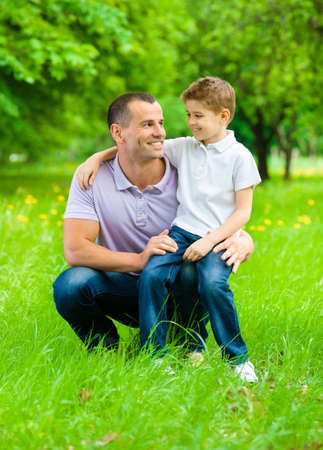 Father keeps son on the knee in the park. Concept of happy family relations and carefree leisure time photo