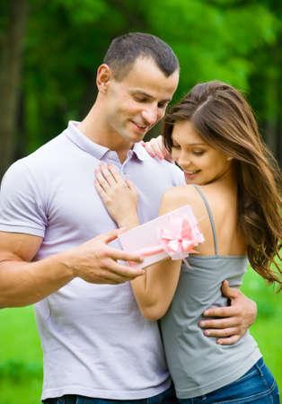 hacer el amor: El hombre da regalo envuelto en papel rosa a la mujer en el parque. Concepto del amor y la sorpresa inesperada
