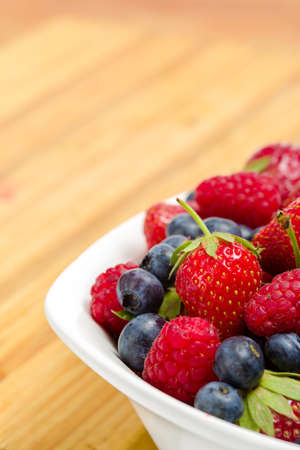 Close-up view of part of plate full of berries on the table. Concept of healthy eating and dieting lifestyle photo