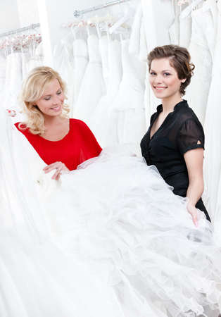 Two girls compare the wedding dress preparing to try it on photo