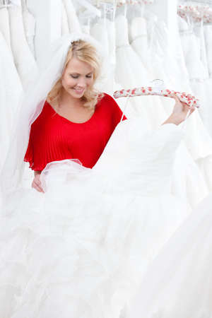 Bride is eager to try wedding dress on, on white background photo