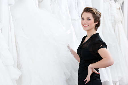 Shop assistant picks out the dress and hesitates should the bride try this particular dress or not photo