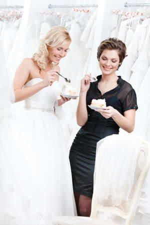 Shop assistant and the bride eat a delicious cake selebrating a good decision photo