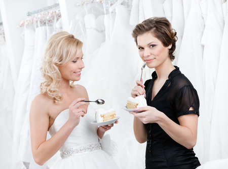 amasing: Shop assistant and the bride eat an amasing wedding cake Stock Photo
