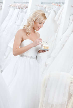 Happy bride tastes wedding pie, white background photo