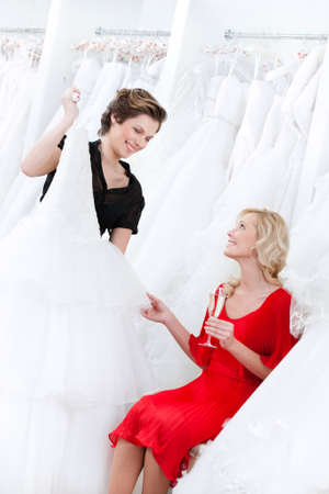 selects: Shop assistant suggests another dress to the bride while she is drinking champagne