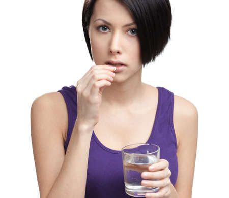 Woman with glass of water takes drugs, isolated on white. Medication pills photo
