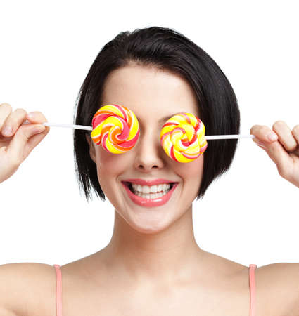 Smiley woman keeps lollypops on the eyes, isolated on white Stock Photo - 25595543
