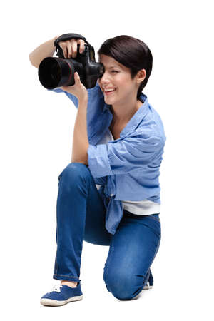 Girl-photographer takes shots, isolated on white